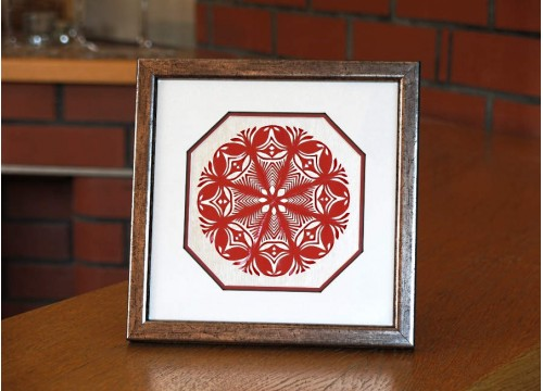 A Red Kurpie star in a silvery frame